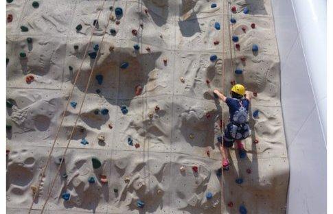 YQ climbs a rock climbing wall